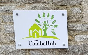A sign with the logo and title of Combe hub