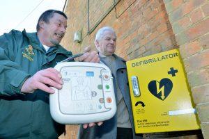 An ambulance office installing a community defibrillator