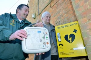 An ambulance office installing a community defibrillator